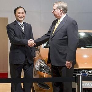Li Shufu, pela Geely, e Lewis Booth, pela Ford, cumprimentam-se neste domingo em Gotemburgo, na Suécia, no anúncio da venda da Volvo à empresa chinesa; atrás deles, um exemplar do sedã S60, renovado pela Volvo este ano