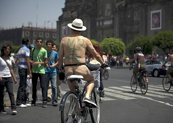 """Ciclista protesta contra uso de carros e em favor das bikes na Cidade do México (em suas costas lê-se """"No + coches""""); naquele país, comércio de veículos seminovos e usados dos EUA deprime produção e demanda por carros novos, forçando baixa nos preços - AFP"""